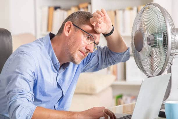 man sweating at home in front of fan